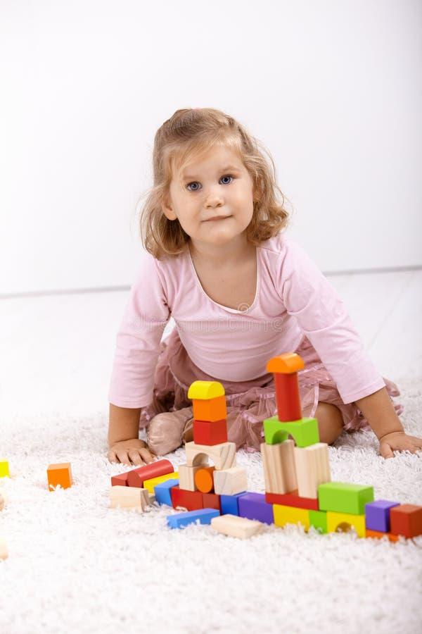 Het spelen van het meisje op vloer thuis royalty-vrije stock afbeelding