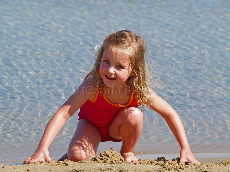 Het spelen van het meisje in zand stock foto's