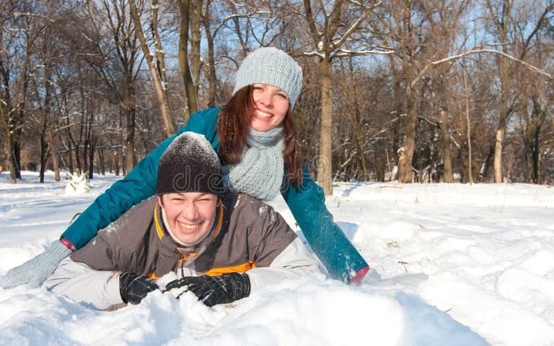 Het spelen van het paar in sneeuw stock afbeeldingen