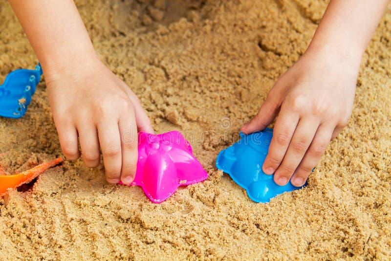 Het spelen van het kind in de zandbak stock afbeelding