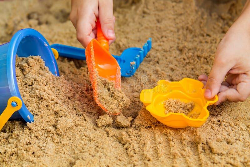 Het spelen van het kind in de zandbak stock foto's