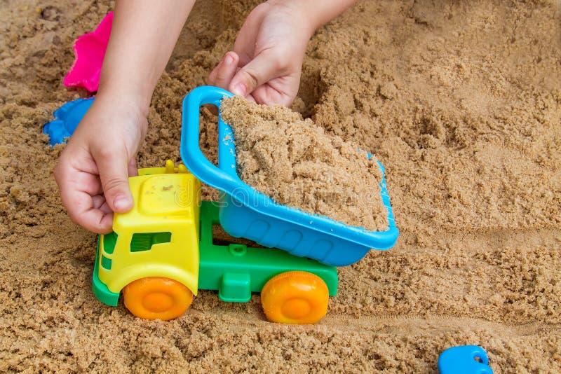 Het spelen van het kind in de zandbak stock foto