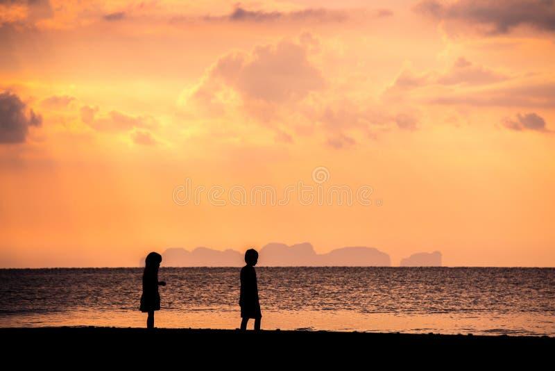 Het spelen van kinderen op het strand bij de zonsondergang Silhouetkind en tropische hemel in zomer stock foto