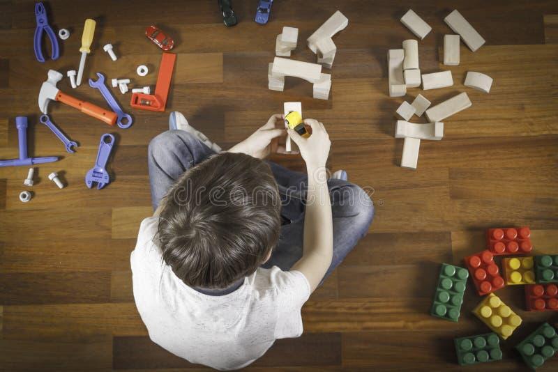 Het Spelen van Little Boy met Speelgoed Jong geitjezitting op de houten vloer in zijn ruimte Hoogste mening royalty-vrije stock afbeeldingen