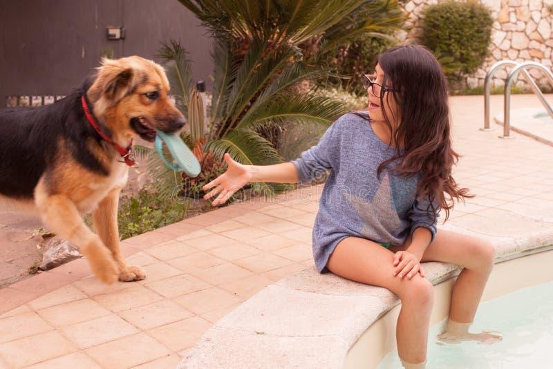 Het spelen van het meisje met haar hond stock afbeelding