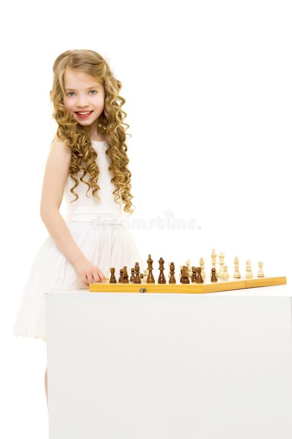 Het spelen van het meisje schaak Een klein meisje speelt schaak Het concept creatief onderwijs die van een kind, opleiden van stock foto