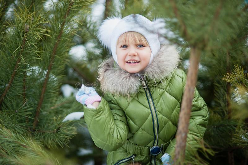 Het spelen van het meisje sneeuwballen Grappig meisje die pret in de winterpark hebben makend tot sneeuwballen gelukkig kindmeisj stock foto's