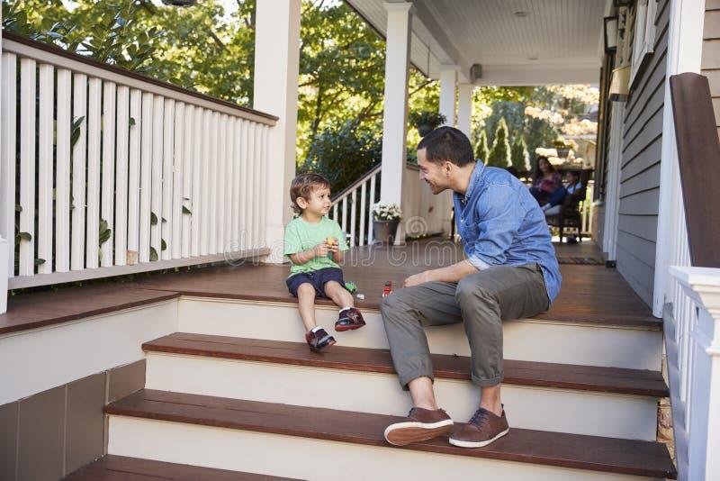 Het Spelen van vaderand son Sit On Porch Of House met Speelgoed samen royalty-vrije stock afbeeldingen