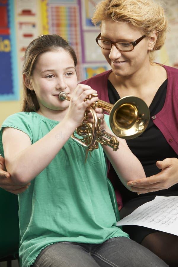 Het Speltrompet van leraarshelping pupil to in Muziekles stock foto