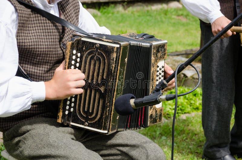 Het spelvolksmuziek van de accordeonistmens met harmonika stock fotografie