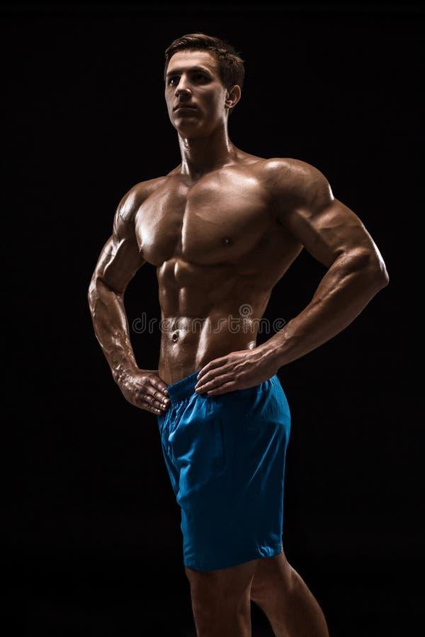 Het spier en geschikte jonge bodybuildergeschiktheid mannelijke model stellen over zwarte achtergrond stock foto