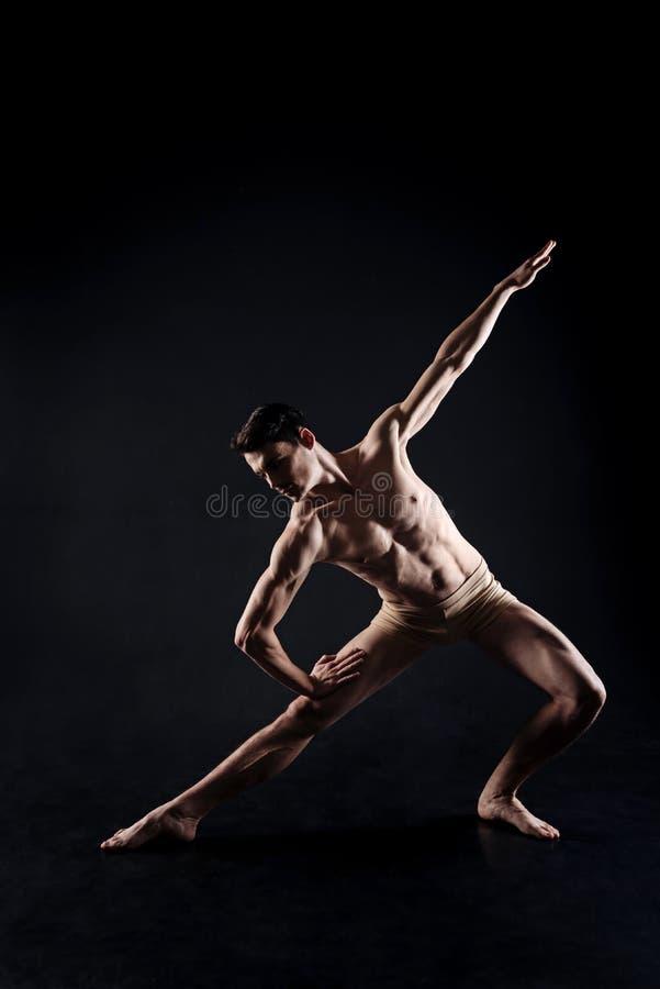 Het spier jonge atleet uitrekken zich in de zwarte studio stock afbeelding