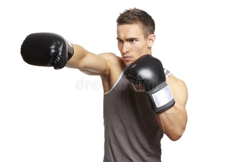 Het spier jonge mens in dozen doen in sportenuitrusting stock afbeeldingen