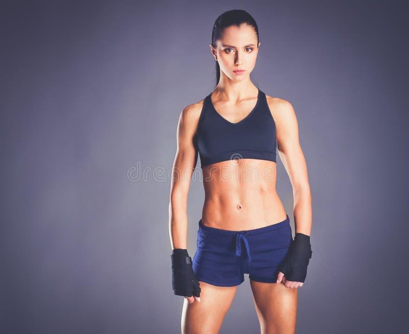 Het spier jonge vrouw stellen in sportkleding tegen zwarte achtergrond stock fotografie