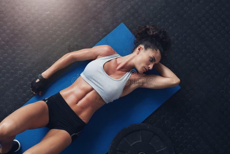 Het spier jonge vrouwelijke atleet ontspannen na training royalty-vrije stock afbeeldingen