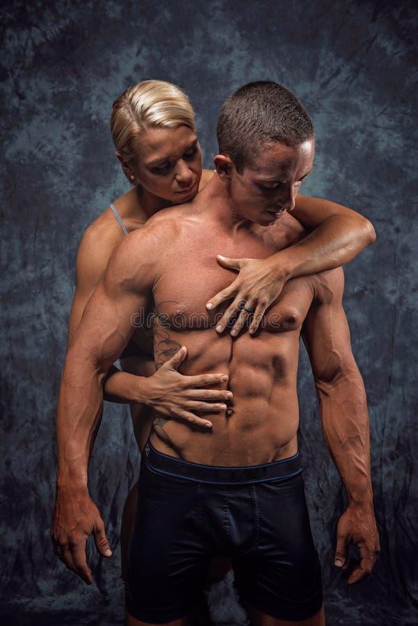 Het spierpaar omhelzen stock foto