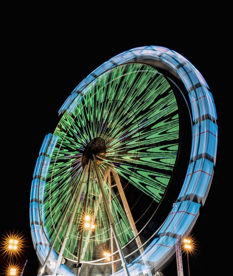 Het spinnen ferris rijden bij nacht in een park van afleiding met mooie kleuren royalty-vrije stock afbeeldingen