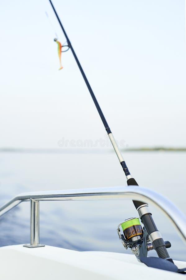 Het spinnen met het met een sleeplijn vissen op de schip` s schil agains royalty-vrije stock foto's