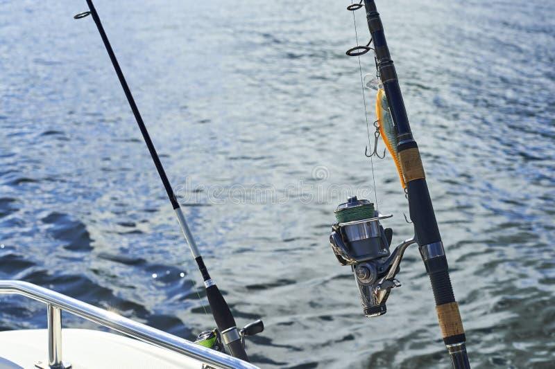 Het spinnen met het met een sleeplijn vissen op de schip` s schil tegen de achtergrond stock afbeelding