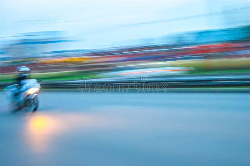Het spitsuur van de stadsavond met motorrijder het verzenden stock afbeelding