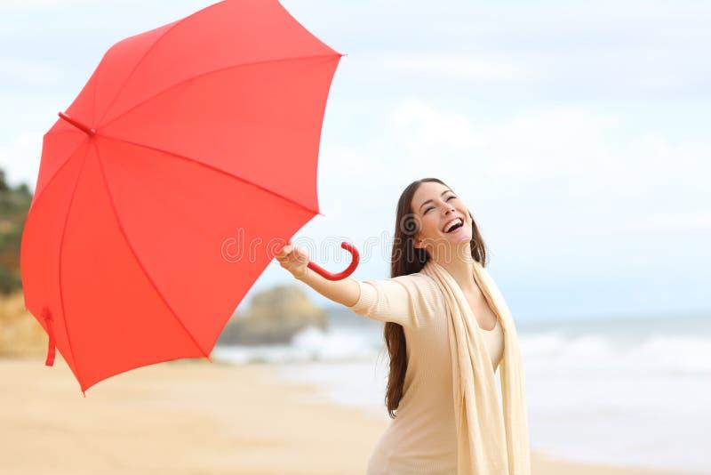 Het spontane vrouw spelen met een rode paraplu op het strand royalty-vrije stock fotografie