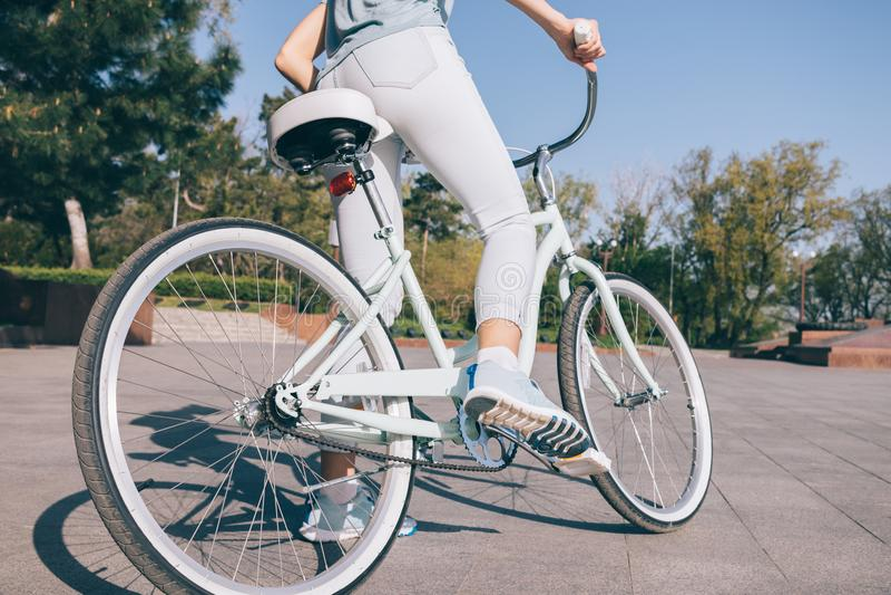 Het sportenmeisje in jeans en tennisschoenen zit op een fiets royalty-vrije stock fotografie