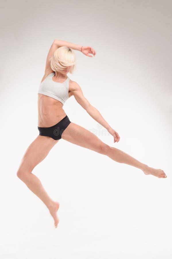 Het sportieve blonde toont acrobatische oefeningen stock foto's