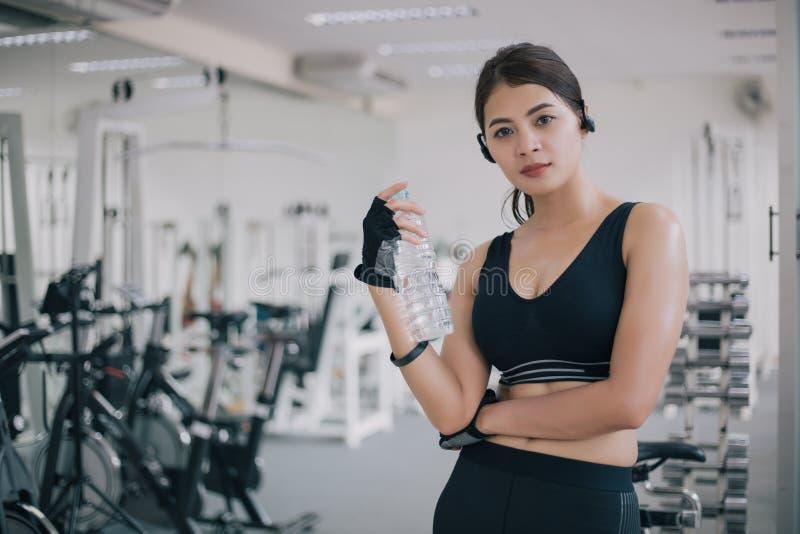 Het sportieve drinkwater van vrouwenazië na oefeningen in de gymnastiek Geschiktheid - concept gezond royalty-vrije stock foto's