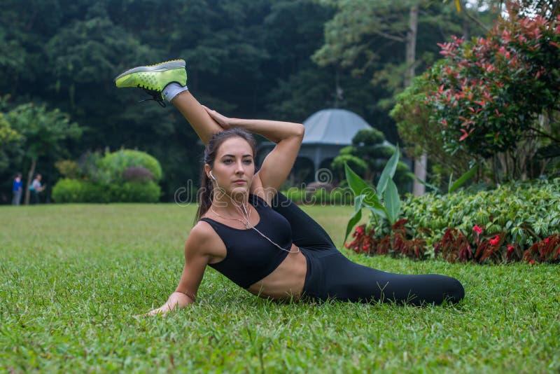 Het sportieve flexibele jonge vrouw doen verlamt uitrekkende oefeningen in openlucht op gras Actieve geschikte meisje opleiding i royalty-vrije stock afbeelding