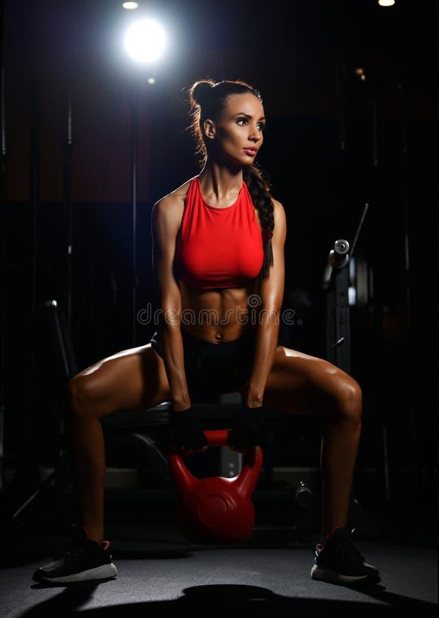 Het sportieve geschiktheidsvrouw uitwerken met gewicht doet hurkzit met domoor in gymnastiek Het op dieet zijn en gewichtsverlies stock fotografie