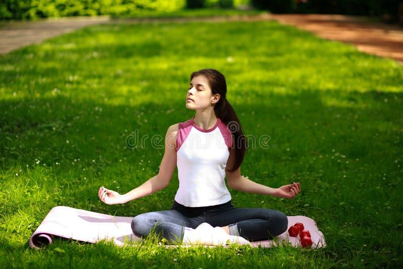 Het sportieve jonge vrouw ontspannen in zonneschijn, die yogaoefeningen doen stock afbeeldingen