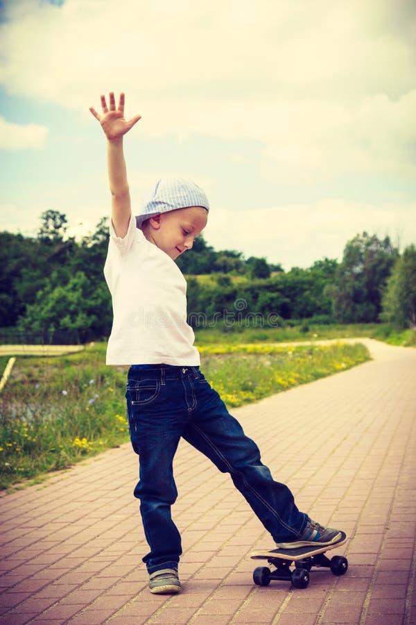 Het sportieve jongenskind openlucht met een skateboard rijden stock foto's