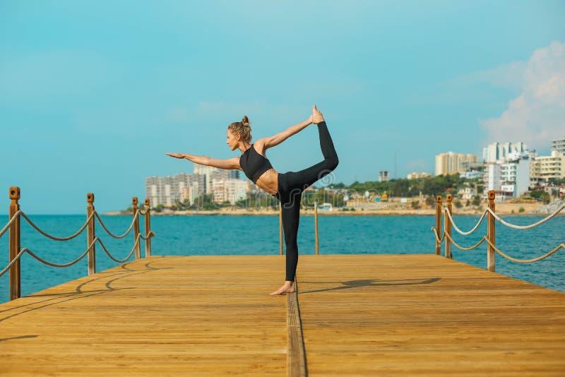 Het sportieve meisje oefent yoga op de kust uit royalty-vrije stock fotografie
