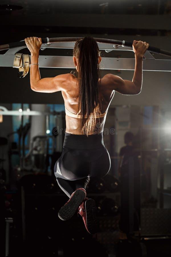 Het sportieve meisje trekt op de rekstok in de gymnastiek uit royalty-vrije stock fotografie