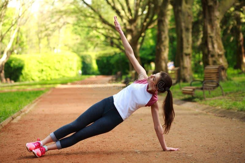 Het sportieve meisje uitoefenen openlucht in park, geschiktheid opleiding royalty-vrije stock fotografie