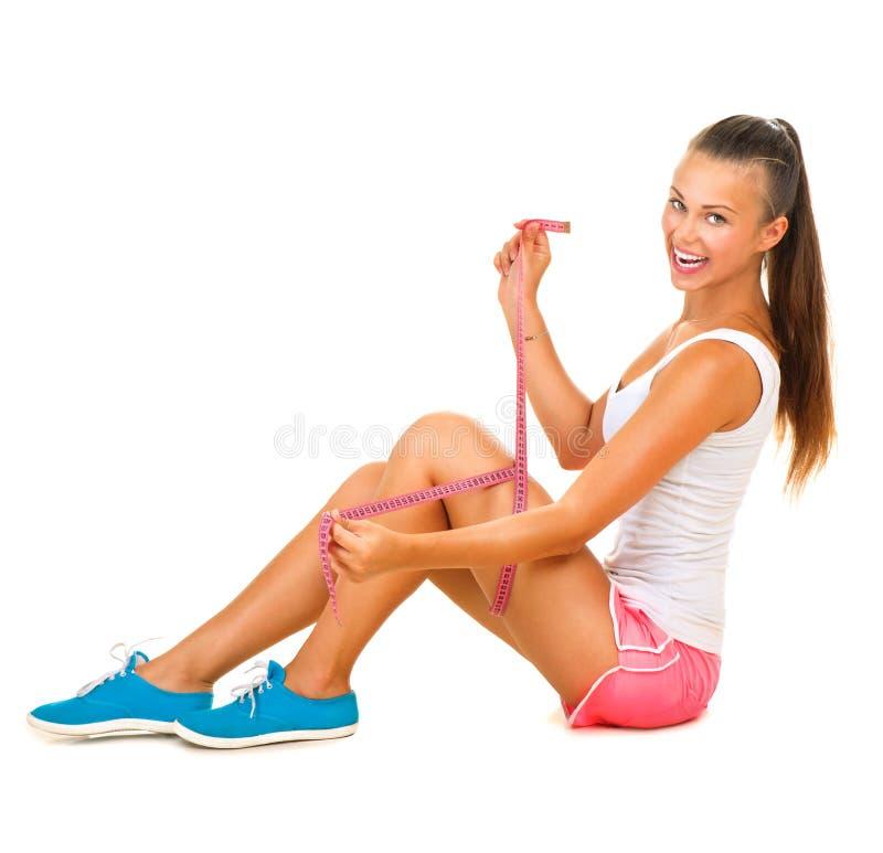 Het sportieve modelmeisje meet haar been stock afbeelding