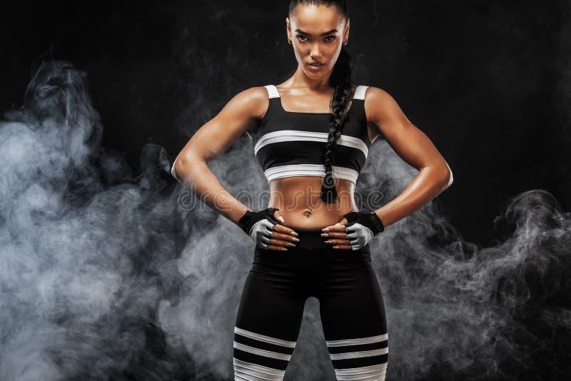 Het sportieve mooie Afro-Amerikaanse model, vrouw in sportwear maakt geschiktheid uitoefenend geschikt bij zwarte achtergrond om  stock afbeelding