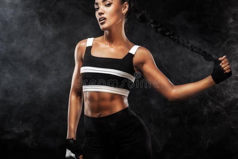 Het sportieve mooie Afro-Amerikaanse model, vrouw in sportwear maakt geschiktheid uitoefenend geschikt bij zwarte achtergrond om  royalty-vrije stock foto's