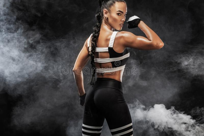 Het sportieve mooie Afro-Amerikaanse model, vrouw in sportwear maakt geschiktheid uitoefenend geschikt bij zwarte achtergrond om  royalty-vrije stock fotografie