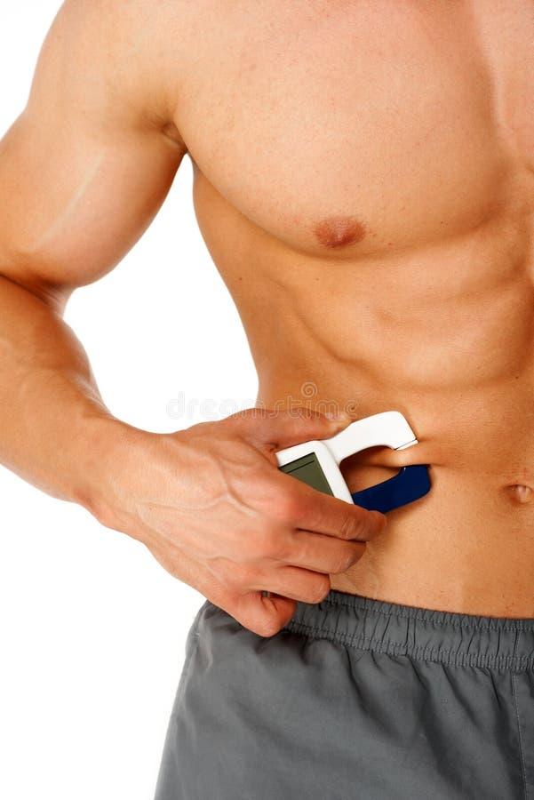 Het sportieve niveau van mensenmaatregelen van vet op zijn lichaam royalty-vrije stock foto's