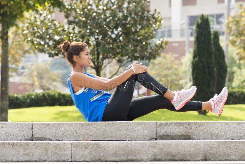 Het sportieve vrouw doen rekt zich alvorens in het park uit te oefenen uit stock foto