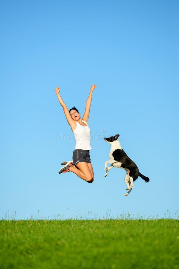 Het sportieve vrouw en hond springen royalty-vrije stock afbeelding