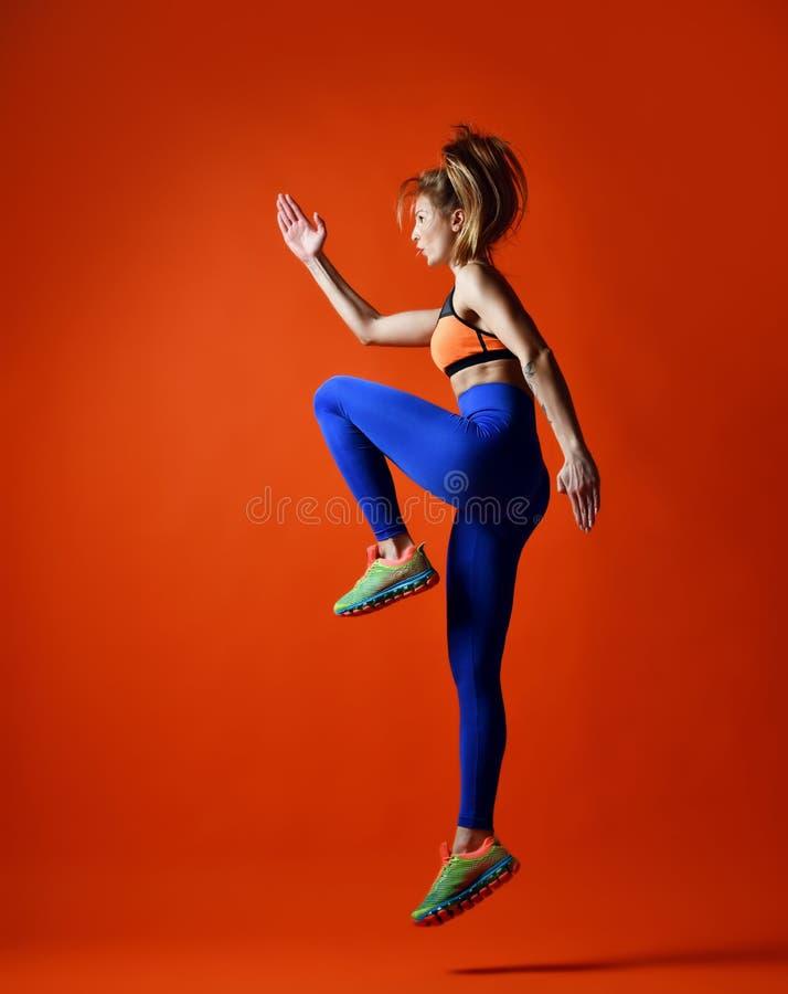 Het sportieve vrouw springen Foto van geschiktheids modeltraining op oranjerode achtergrond royalty-vrije stock afbeelding
