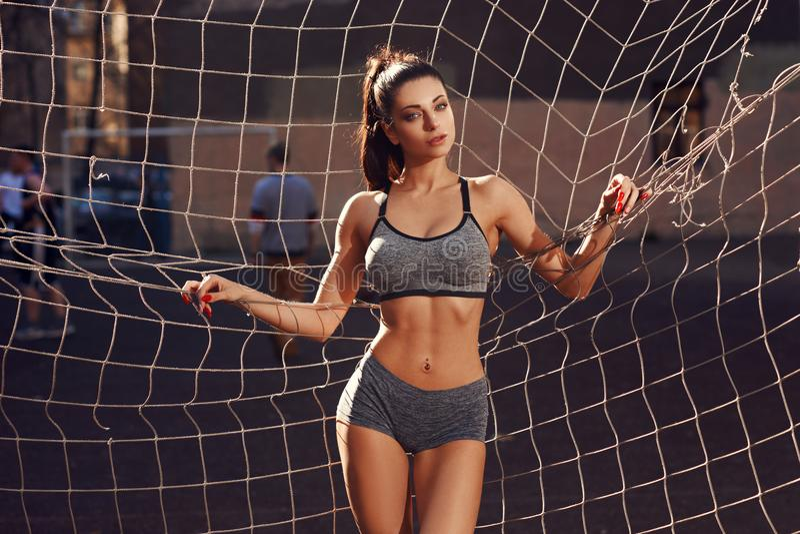 Het sportieve vrouw stellen tegen netto voetbal stock fotografie