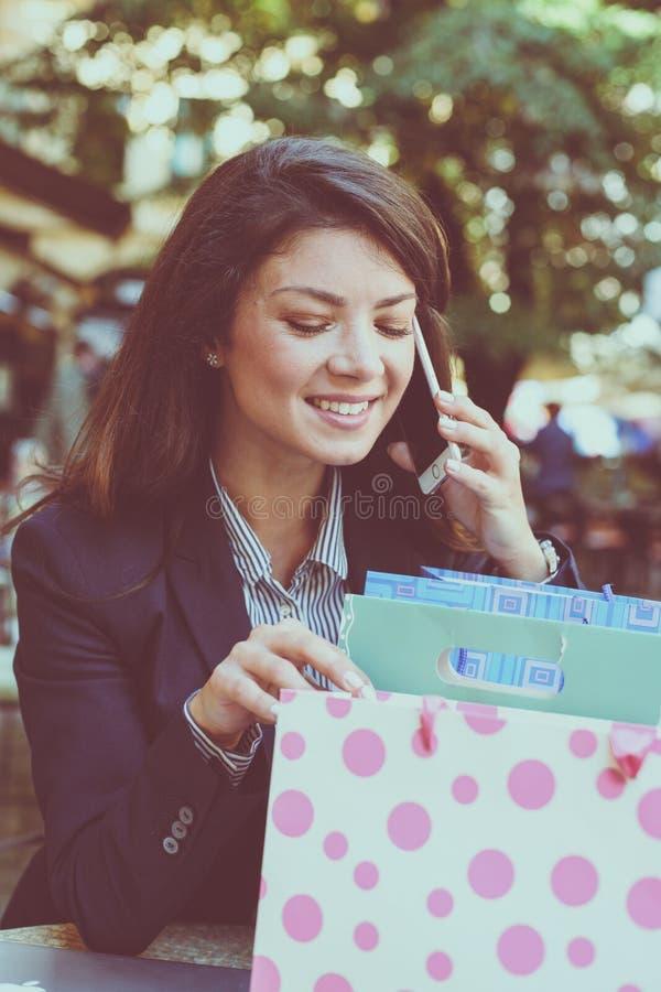 Het spreken aan vriend over het winkelen Jonge Vrouw 15 stock afbeeldingen
