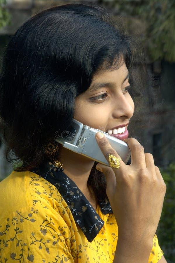 Het spreken bij een mobiele telefoon. stock afbeelding