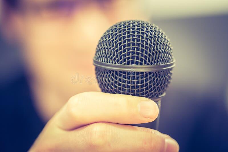 Het spreken in de microfoon: De jonge mens met onscherp gezicht neemt in de microfoon royalty-vrije stock afbeelding