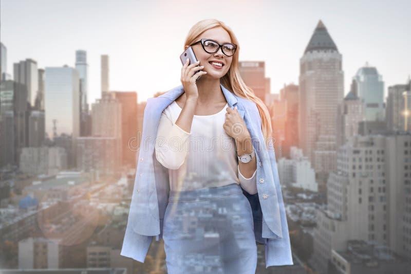 Het spreken met cliënt Vrolijke en jonge bedrijfsdame die in klassieke vrijetijdskleding bij haar smartphone en het glimlachen sp royalty-vrije stock afbeeldingen