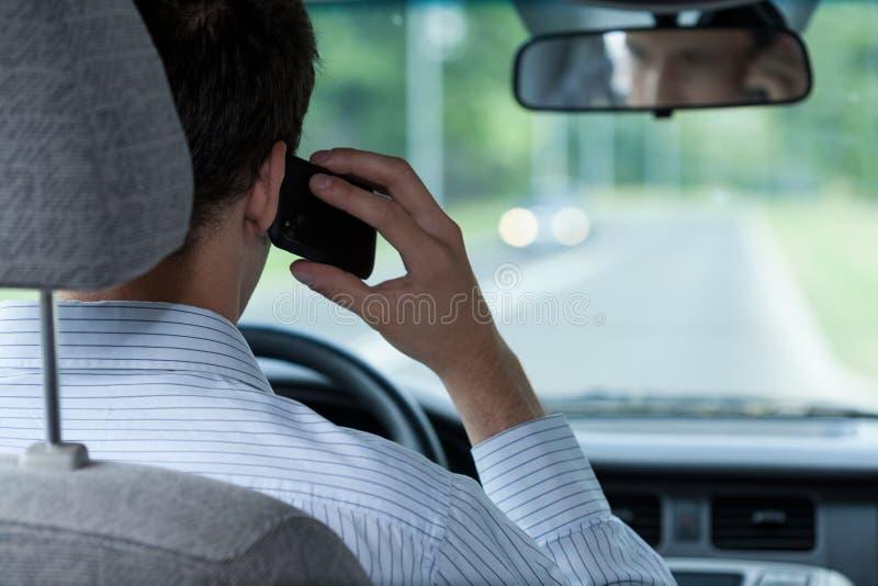 Het spreken op telefoon tijdens drijfauto stock foto's