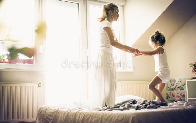 Het springen op bed is pret Meisje met haar moeder royalty-vrije stock afbeeldingen